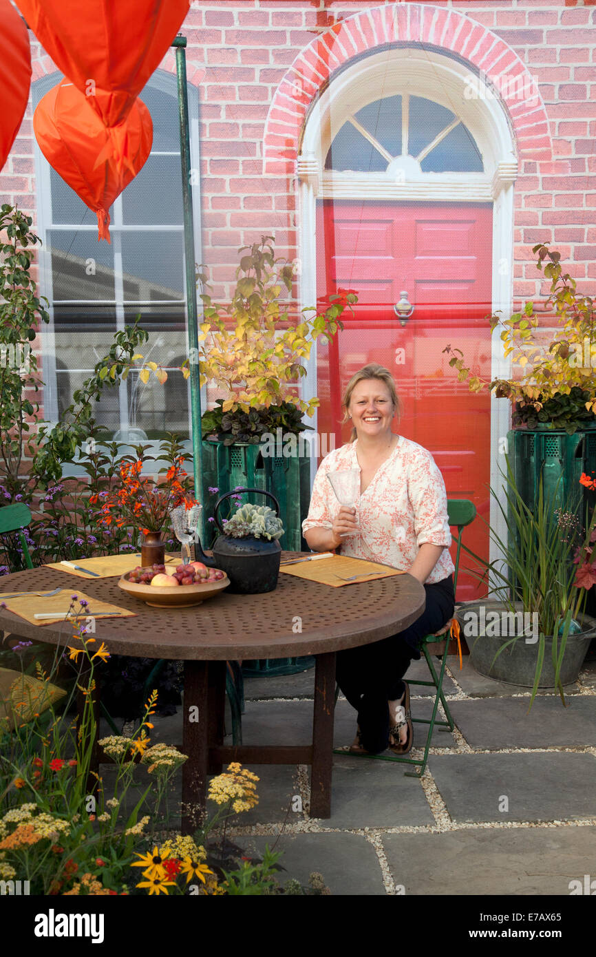 Frau saß im Garten im Innenhof in Harrogate, Yorkshire, UK. 11. September 2014. Lisa Watson mit 'findige' - Grundlagen Stockfoto