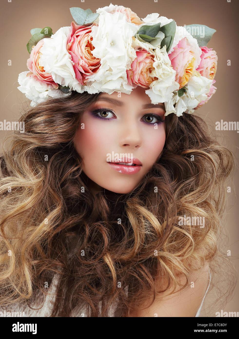 Romantische Frau in Kranz von Blumen mit perfekter Haut und krauses Haar Stockbild