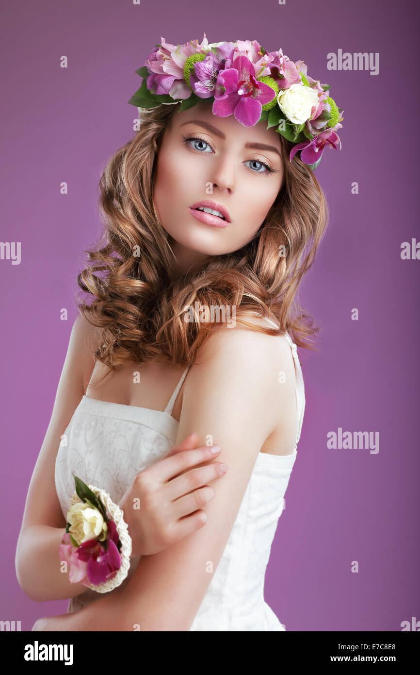 Exquisite Frau mit Kranz aus Blumen. Elegante Dame mit krauses Haar Stockbild