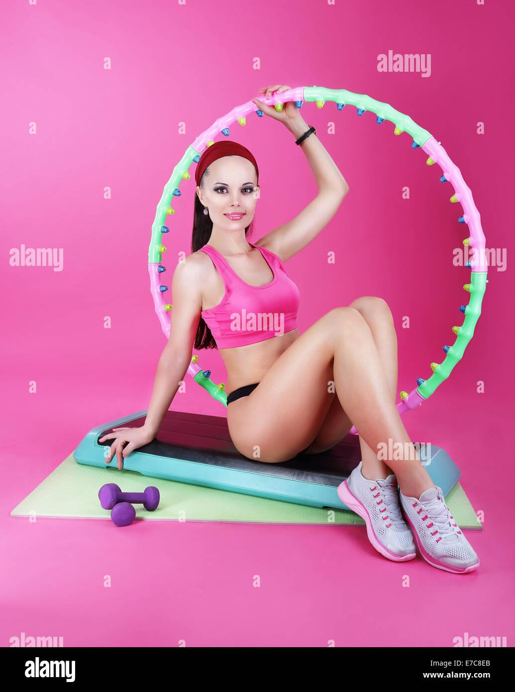 Gesunde Lebensweise. Sportliche Frau sitzt auf der Matte mit Fitnessgeräten Stockbild