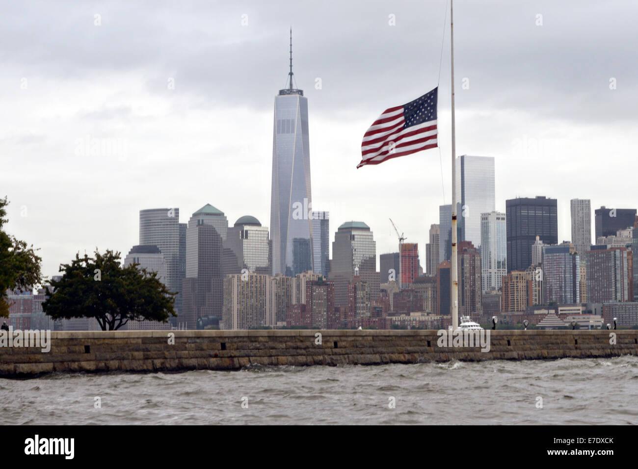 Die amerikanische Flagge auf Halbmast an einem bewölkten Tag mit der Freedom Tower und die Skyline von Manhattan Stockbild