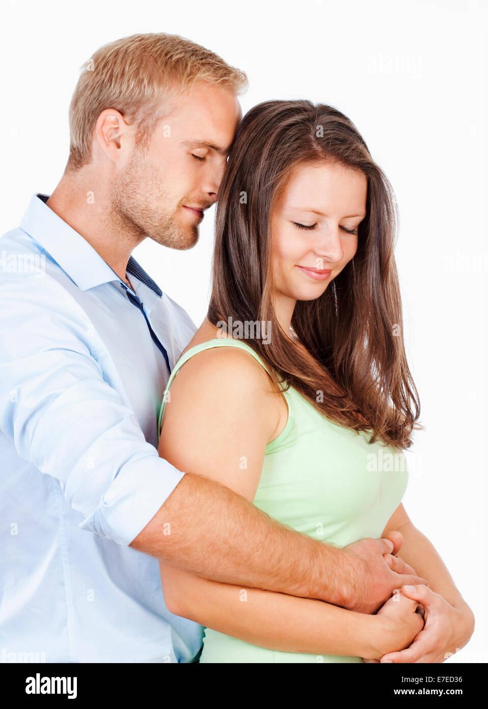 Glückliche junge Paar umarmt mit ihren Augen geschlossen Stockbild