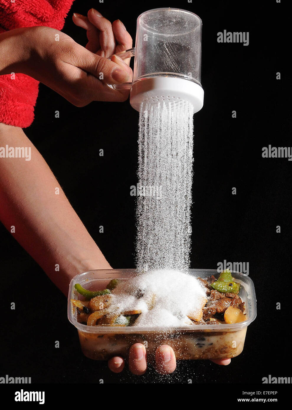 Eine Frau gießt Salz auf eine ungesunde Mahlzeit zum mitnehmen. Stockbild