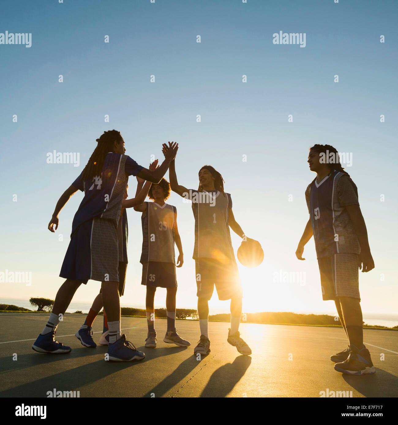 Rückseite beleuchteten Basketball Team hohe Fiving auf Platz Stockfoto