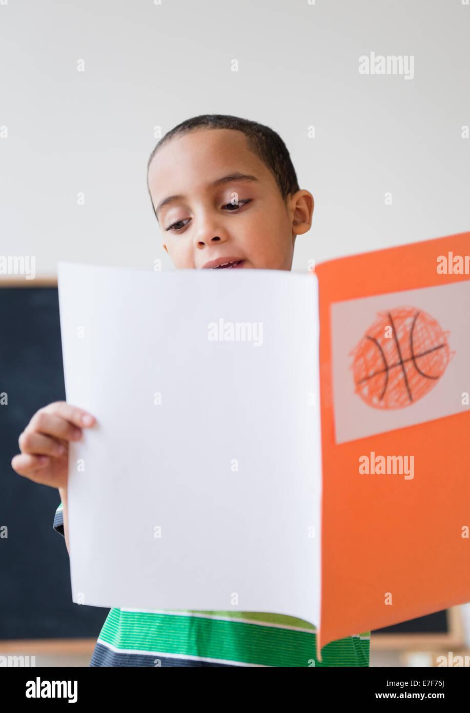 Gemischte Rassen Junge liest Bericht über Basketball in der Klasse Stockfoto