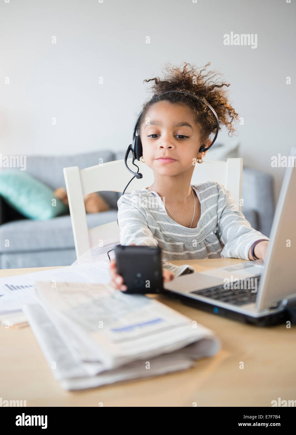 Afroamerikanische Mädchen mit Kopfhörer, Handy und laptop Stockfoto