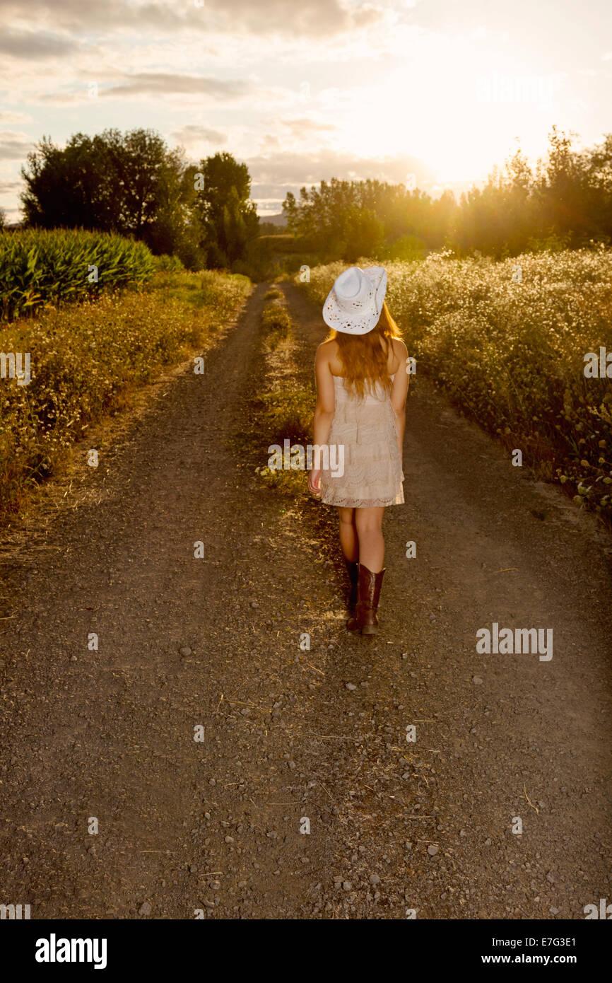 Schönes Landmädchen zu Fuß in Richtung Sonnenuntergang Stockbild