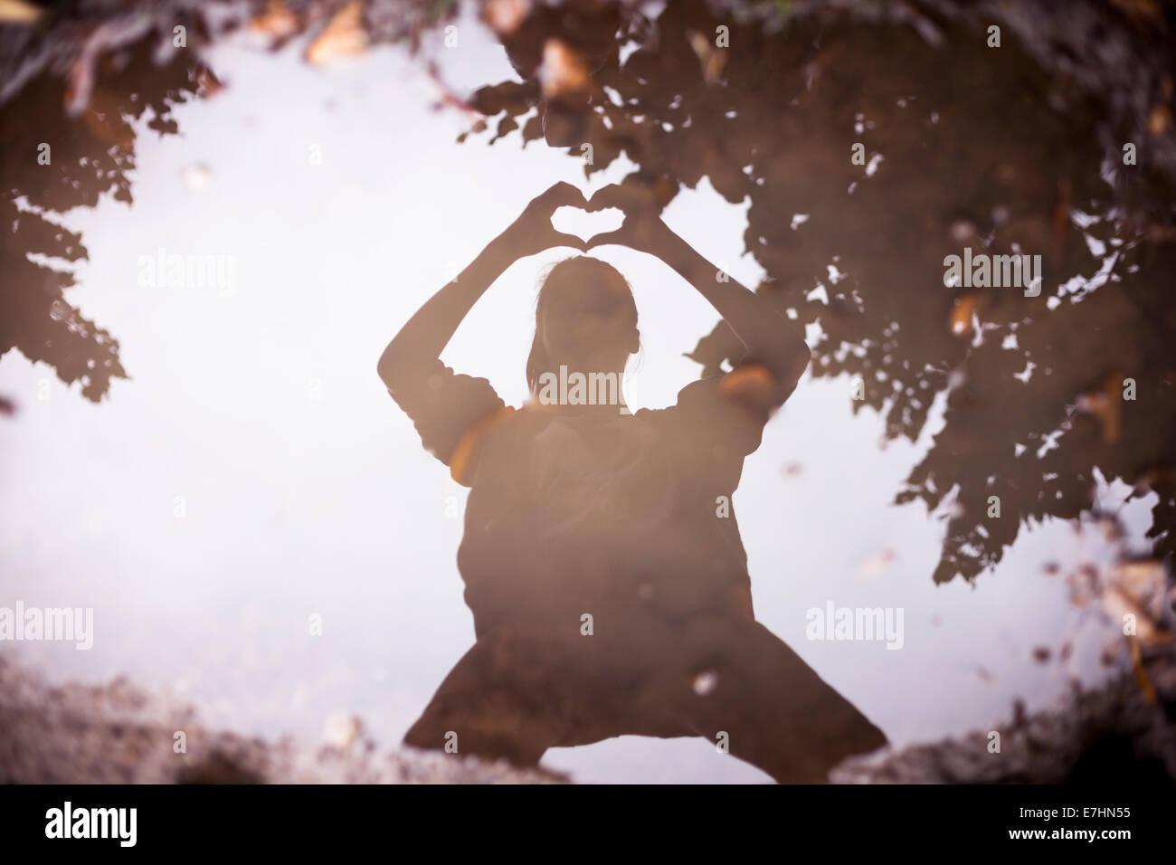 Reflexion in einer Pfütze einer Person, die ein Herz mit seinen Händen formt. Stockbild