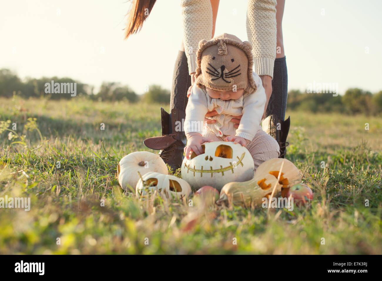 Wenig baby sehen Halloweenkürbis erstmals Stockbild