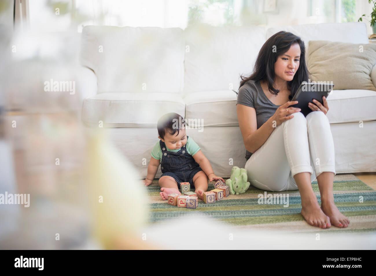 Mutter mit tablet-pc, während ihr Sohn (6-11 Monate) spielen mit Bausteinen Stockbild