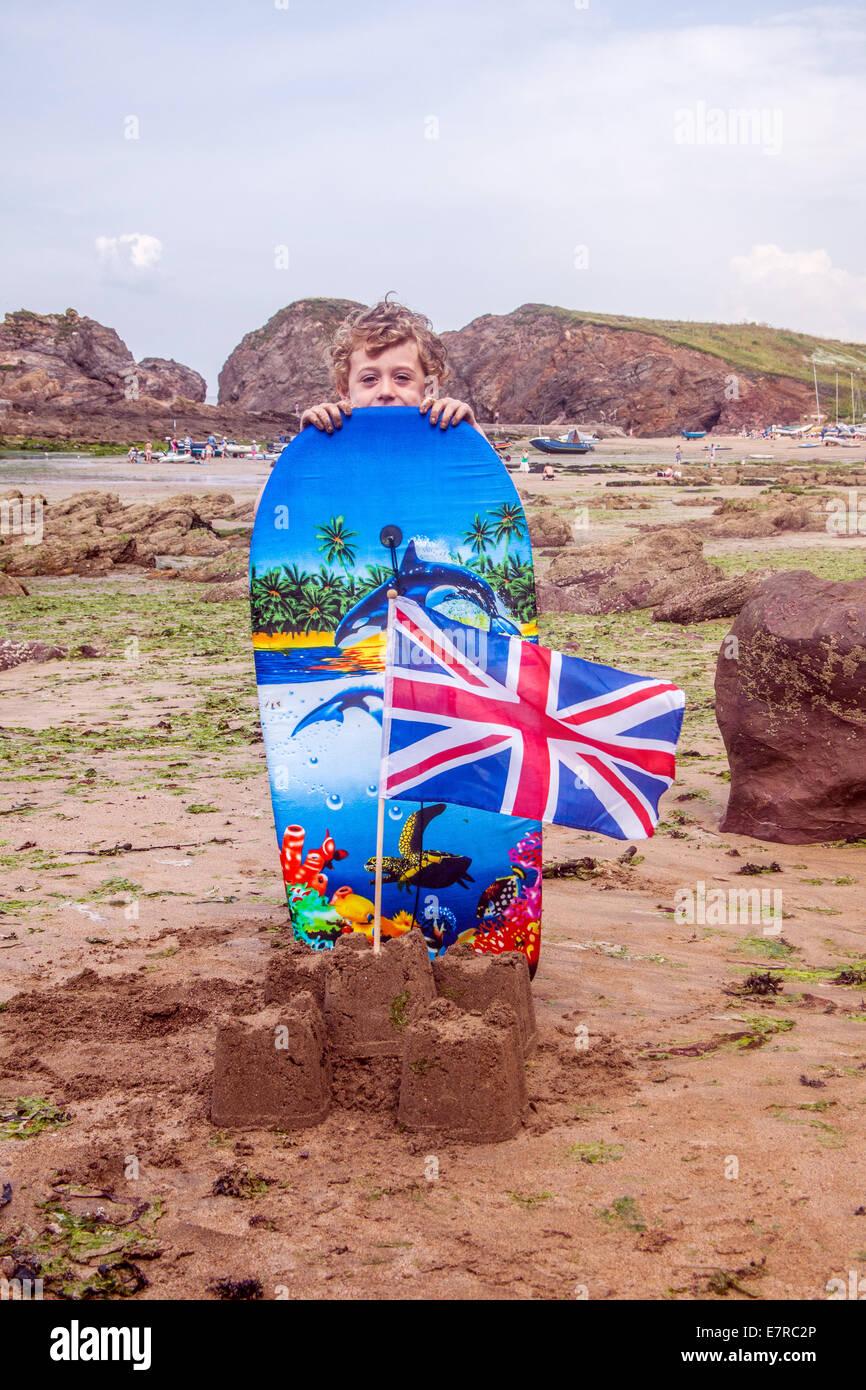 Fünf Jahre alten Jungen mit einer Sandburg und Surfbrett, Hope Cove Beach, South Devon, England, Vereinigtes Stockbild