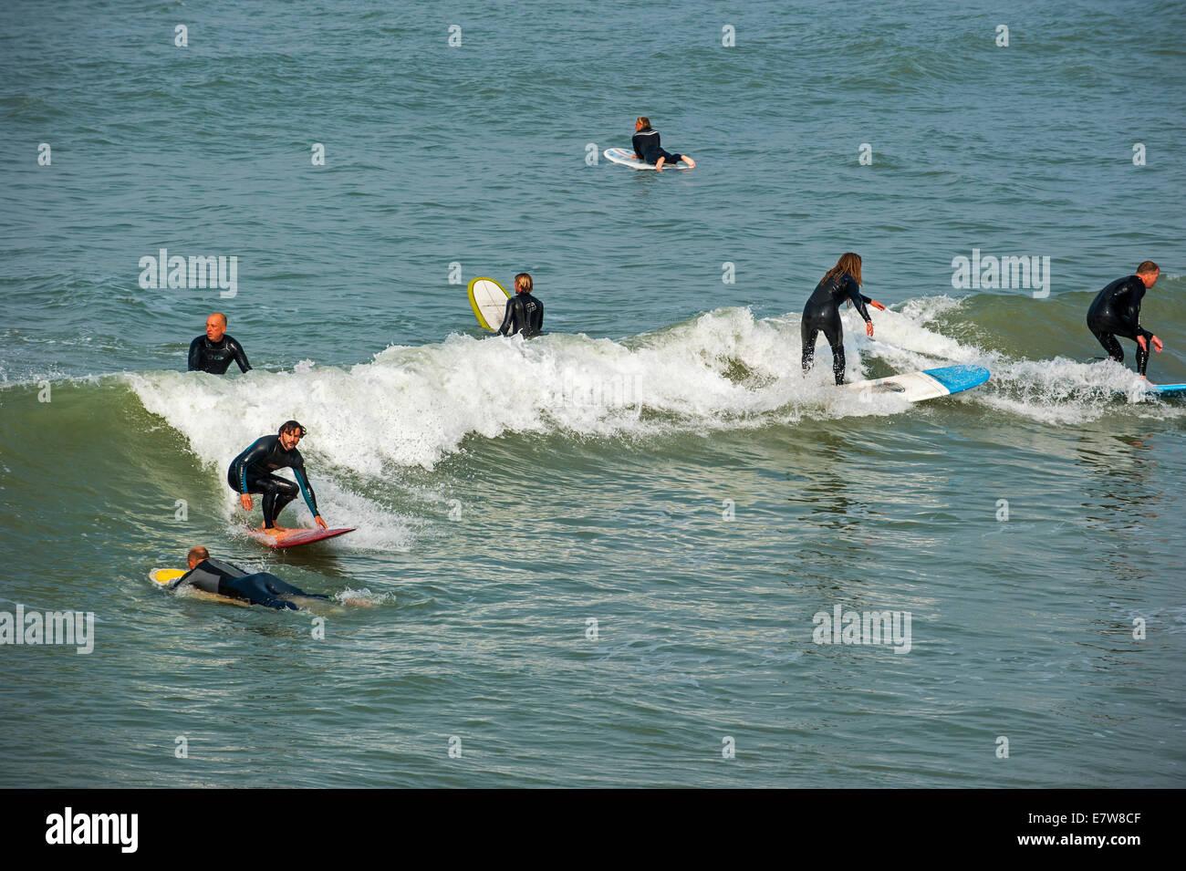 Mittleren Alters Surfer in Neoprenanzüge auf Welle auf Surfboards, wie es auf dem Meer bricht Stockbild