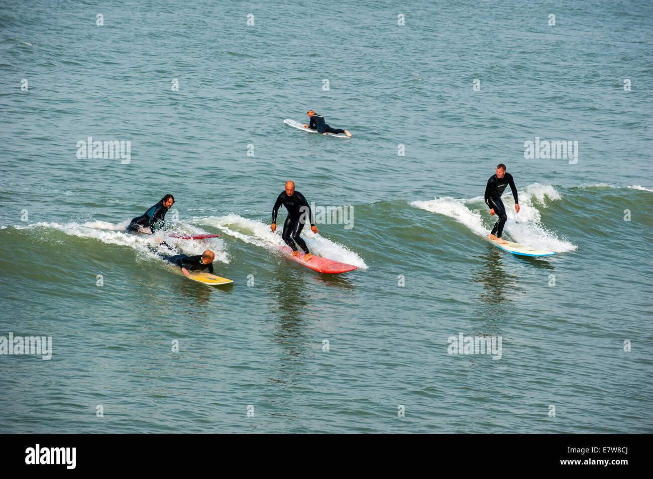 Mittleren Alters Surfer in Neoprenanzüge auf Welle auf Surfboards, wie es auf dem Meer bricht Stockfoto