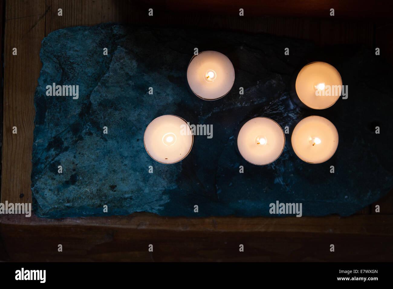 Kerzen strahlen ein warmes Glühen auf einem buddhistischen Schrein Stockfoto