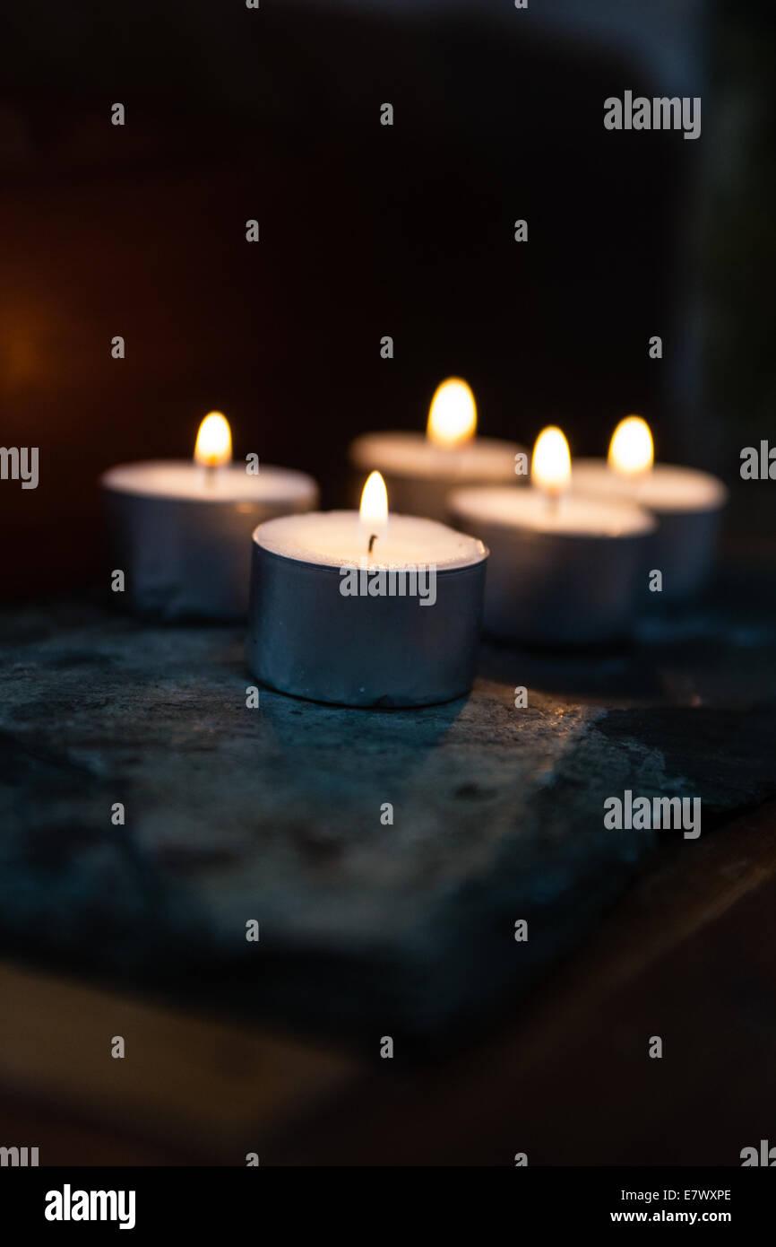 Kerzen strahlen ein warmes Glühen auf einem buddhistischen Schrein Stockbild
