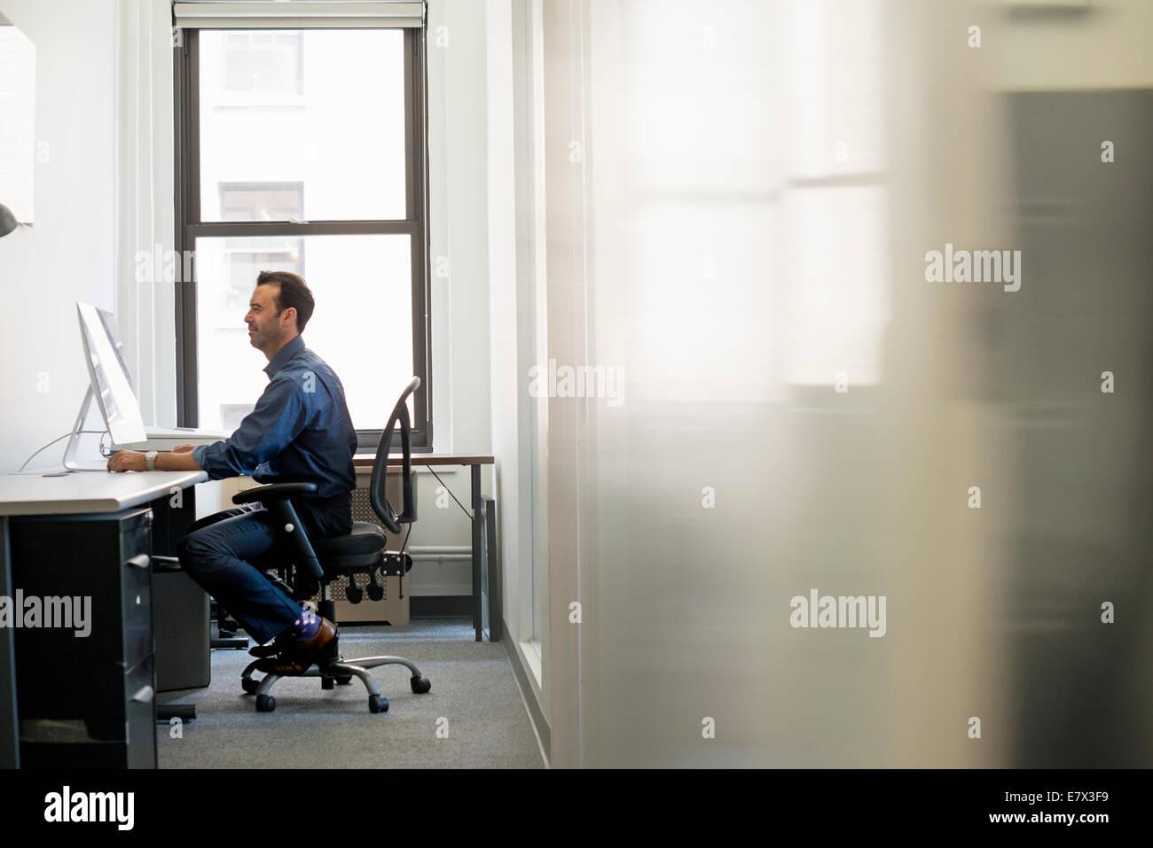 Büroalltag. Ein Mann in Freizeitkleidung sitzen an einem Schreibtisch, einem Computer-Bildschirm betrachten. Stockbild