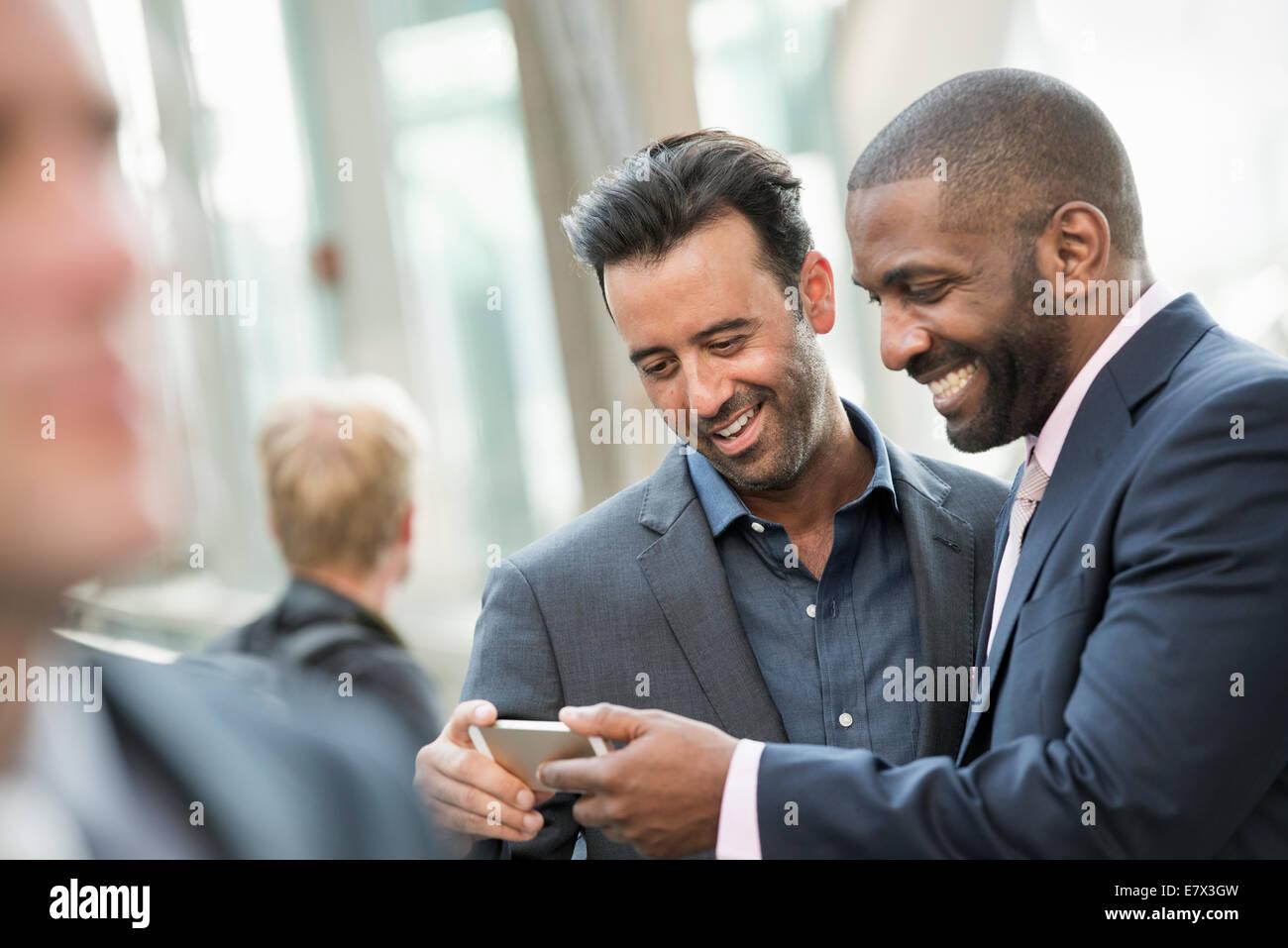 Zwei Männer, die eine Smartphone überprüfen. Stockbild