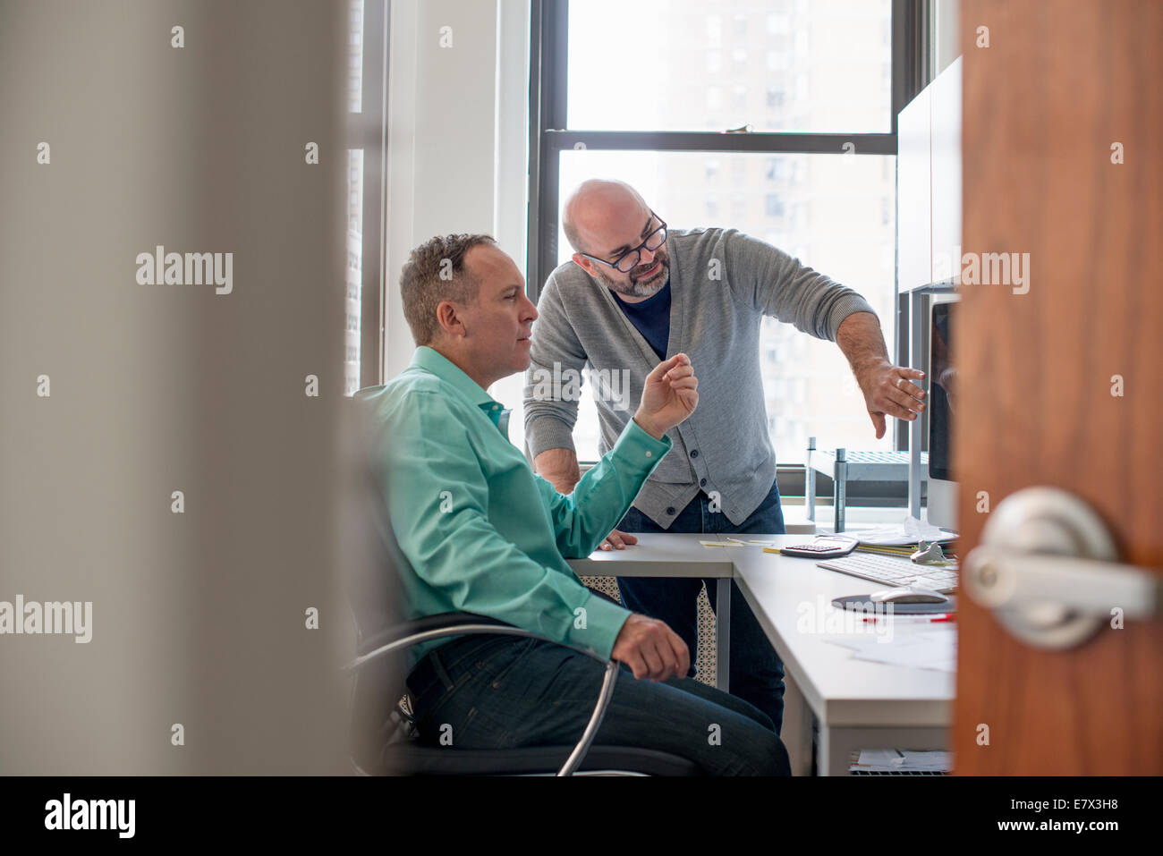Zwei Männer in einem Büro, einem Computer-Bildschirm betrachten. Stockbild