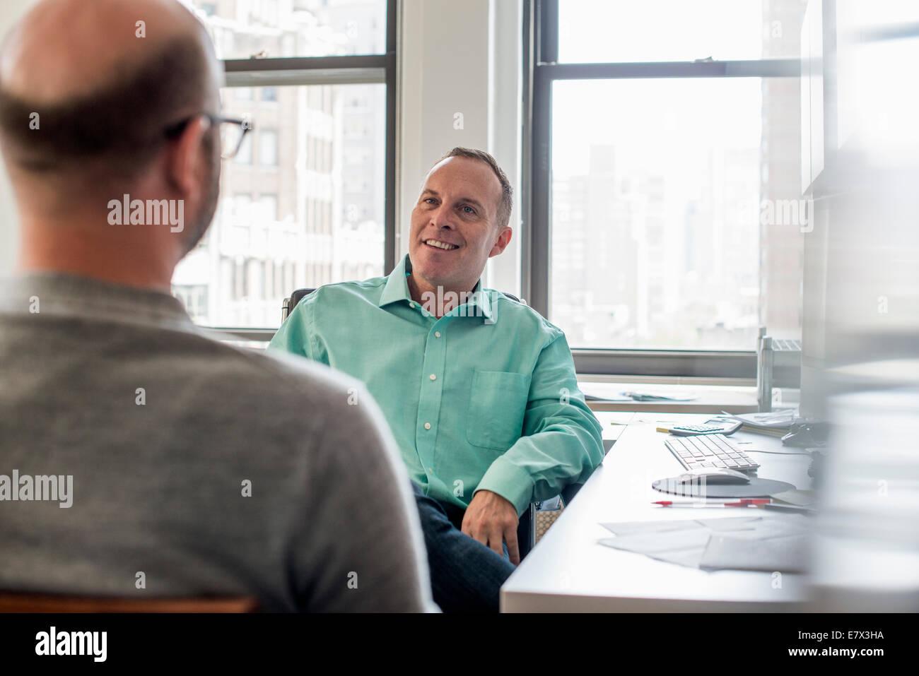 Zwei Männer sitzen in einer hellen luftigen Büroumgebung sprechen. Stockbild