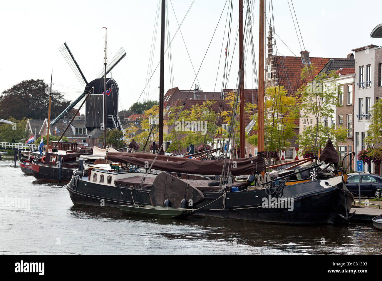 Schiffe im historischen Hafen in die Stadt Leiden, mit im Hintergrund Windmühle de Put Stockbild