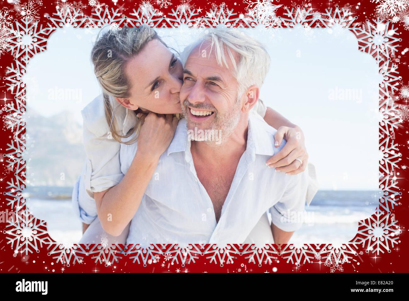 Mann gibt seine lächelnden Frau Huckepack am Strand Stockbild