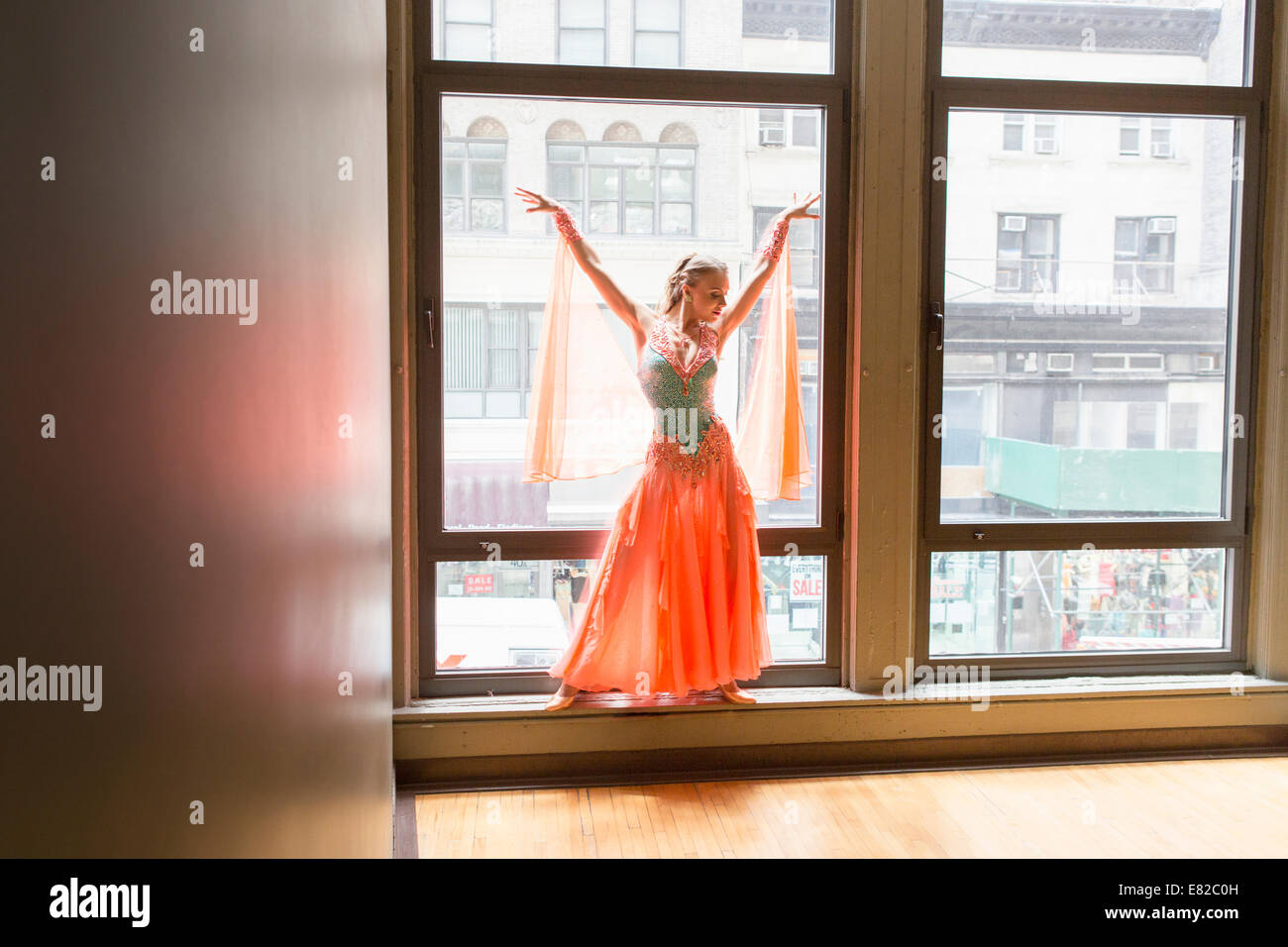 Tänzerin in Tanzstudio. Eine Frau am Fenster posiert. Stockbild