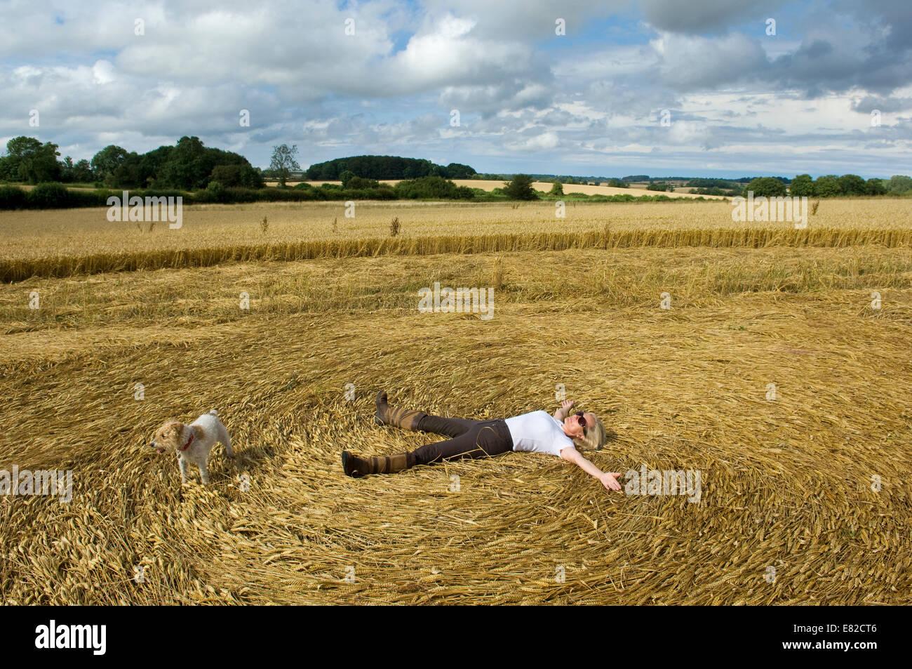 Ein Bauer auf seinem Rücken in die Stoppeln von einem frisch geschnittenen Ernte Feld Erstellen eines Musters Stockbild