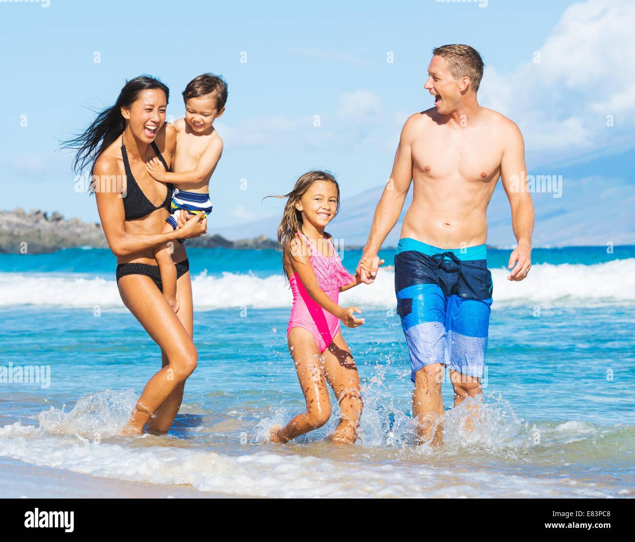 Happy Mixed Race Familie von vier spielen und Spaß am Strand Stockbild
