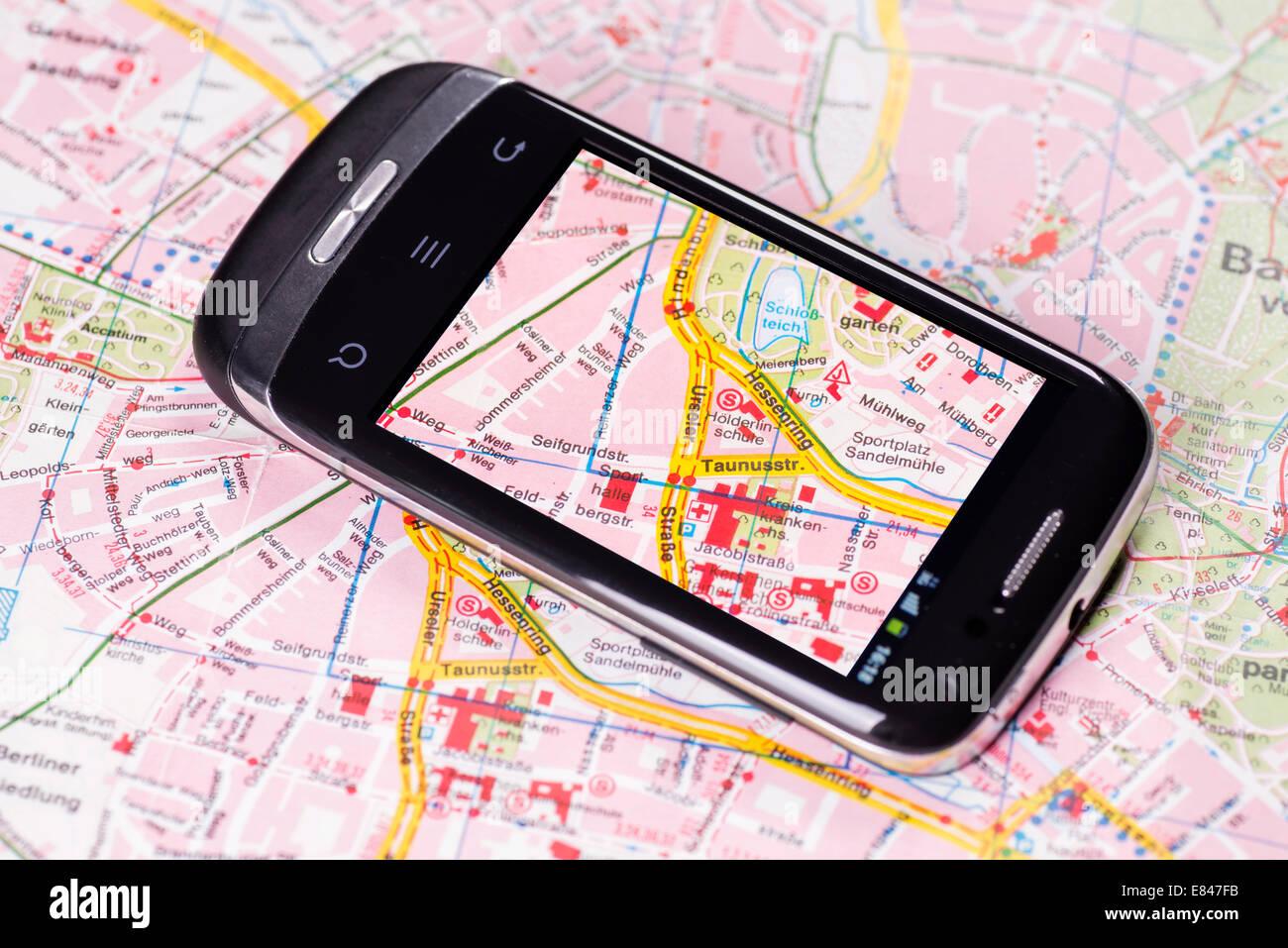 Smartphone mit Kartenansicht befindet sich auf einer gedruckten Karte. Stockbild
