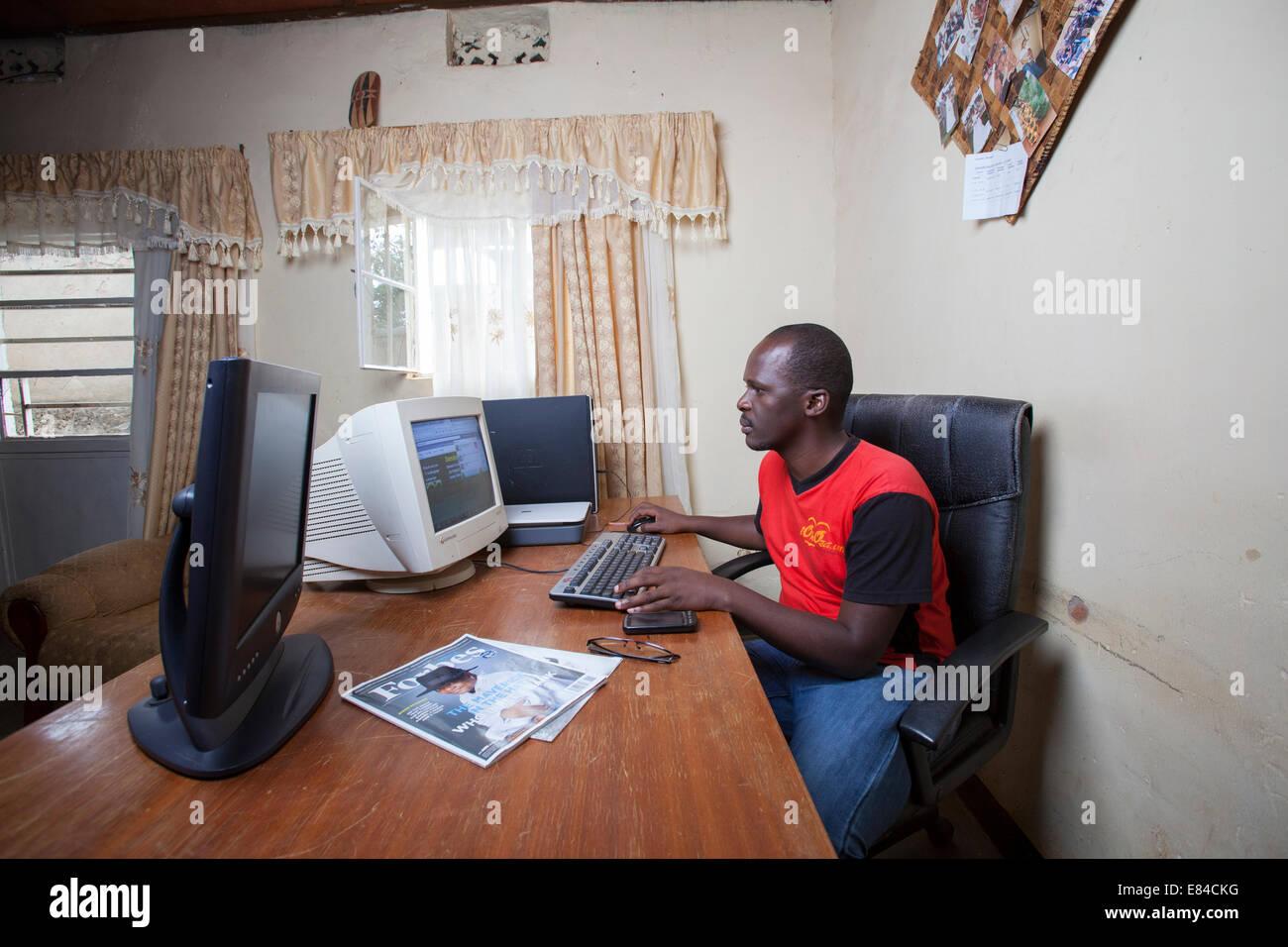 Ruandische Website-Administrator Ausführen eines Online-Geschäfts aus seinem Büro zu Hause, Kigali, Stockbild