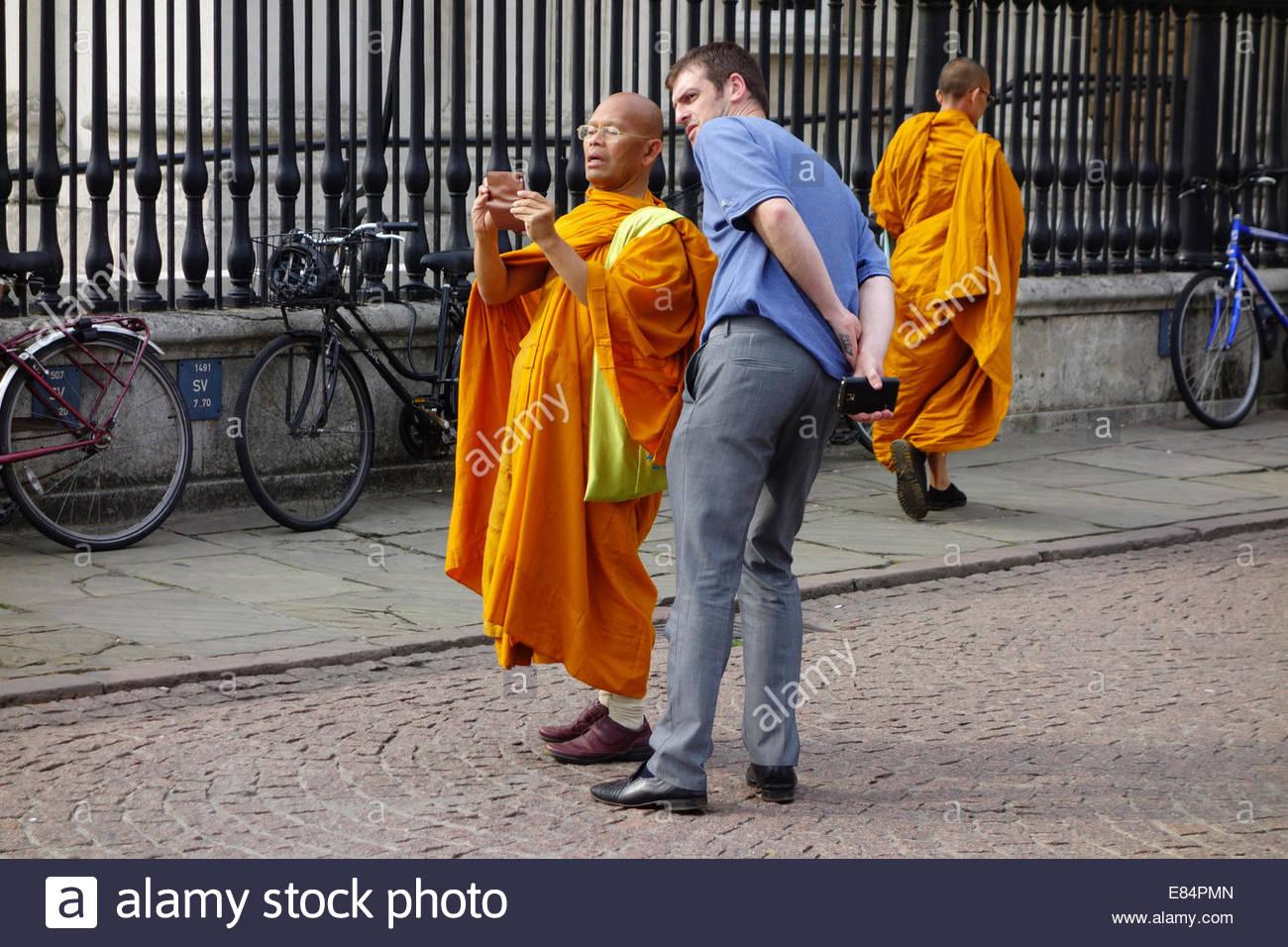 Ein Buddhist sucht Rat über die Verwendung seiner Kamera von einem anderen Touristen auf Kings Parade in Cambridge, Stockbild