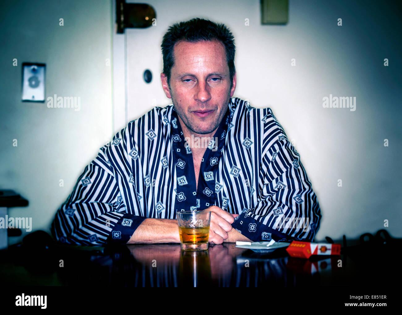 Mann sitzt in seidigen Robe mit Whisky und Zigaretten Stockbild