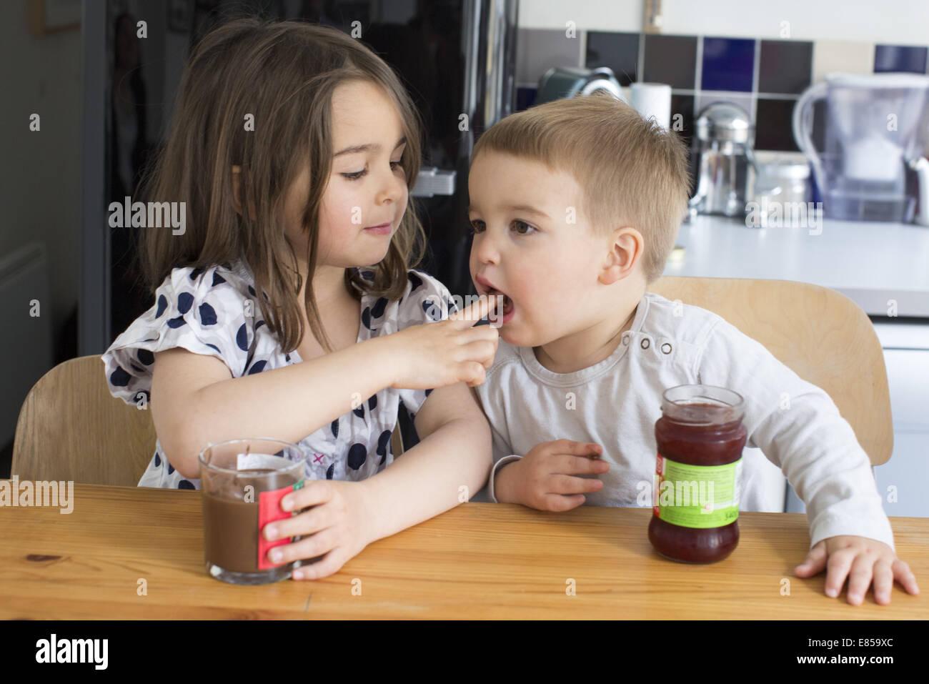 Junge Geschwister Verkostung Inhalt von Gläsern mit ihren Fingern Stockbild