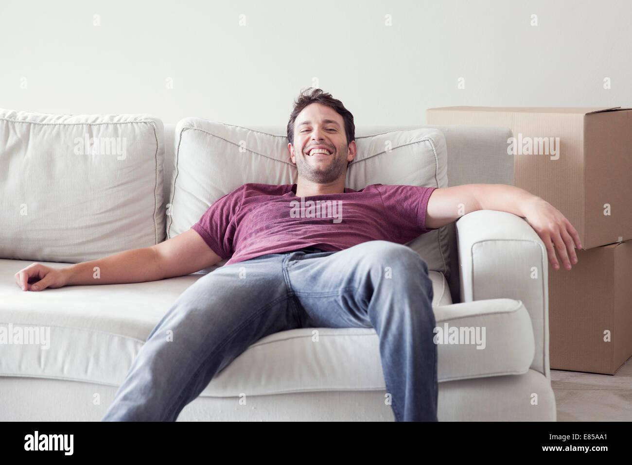 Mann auf Sofa beim Umzug Stockbild