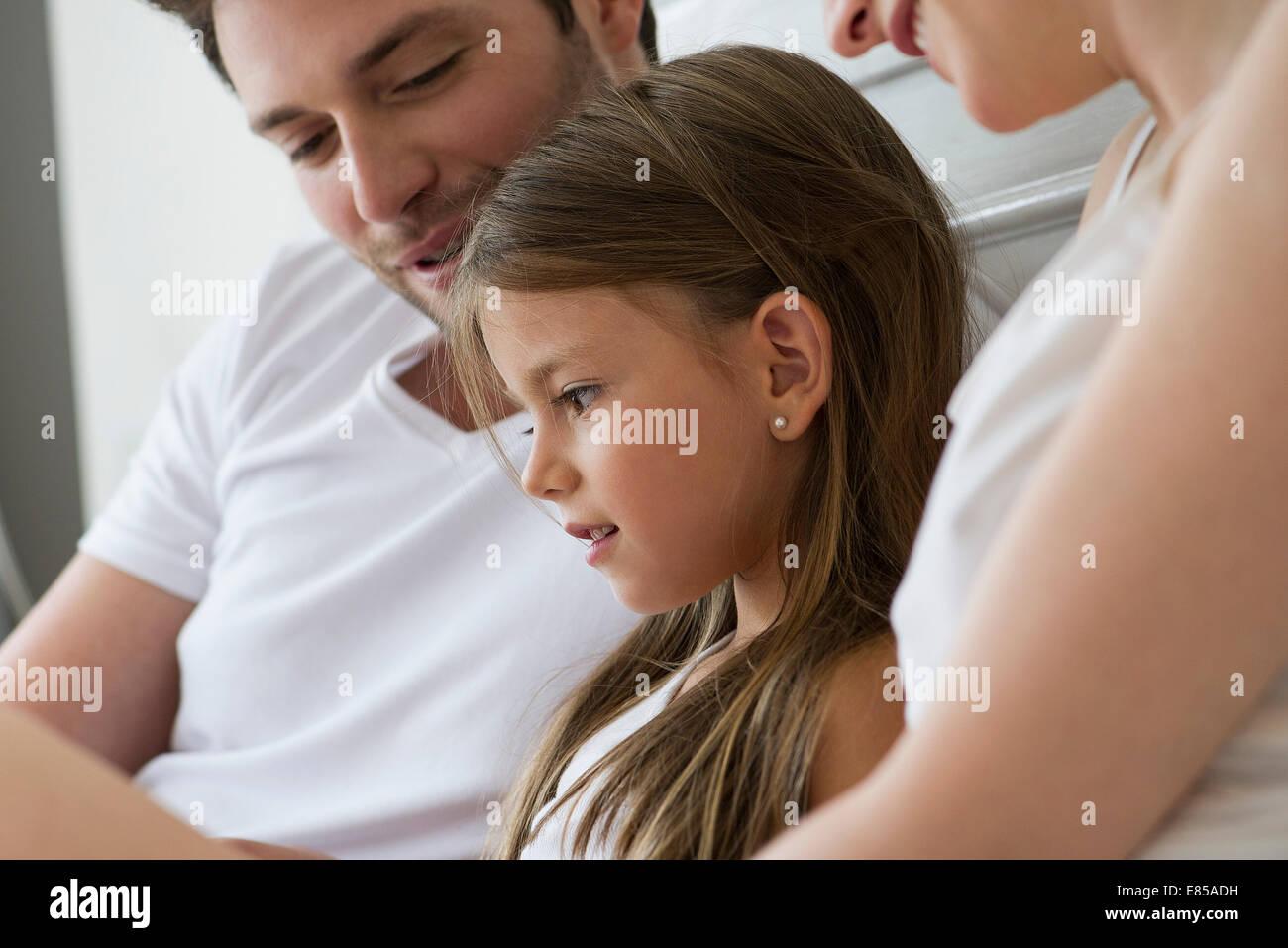 Eltern und Tochter gemeinsam lesen Stockbild