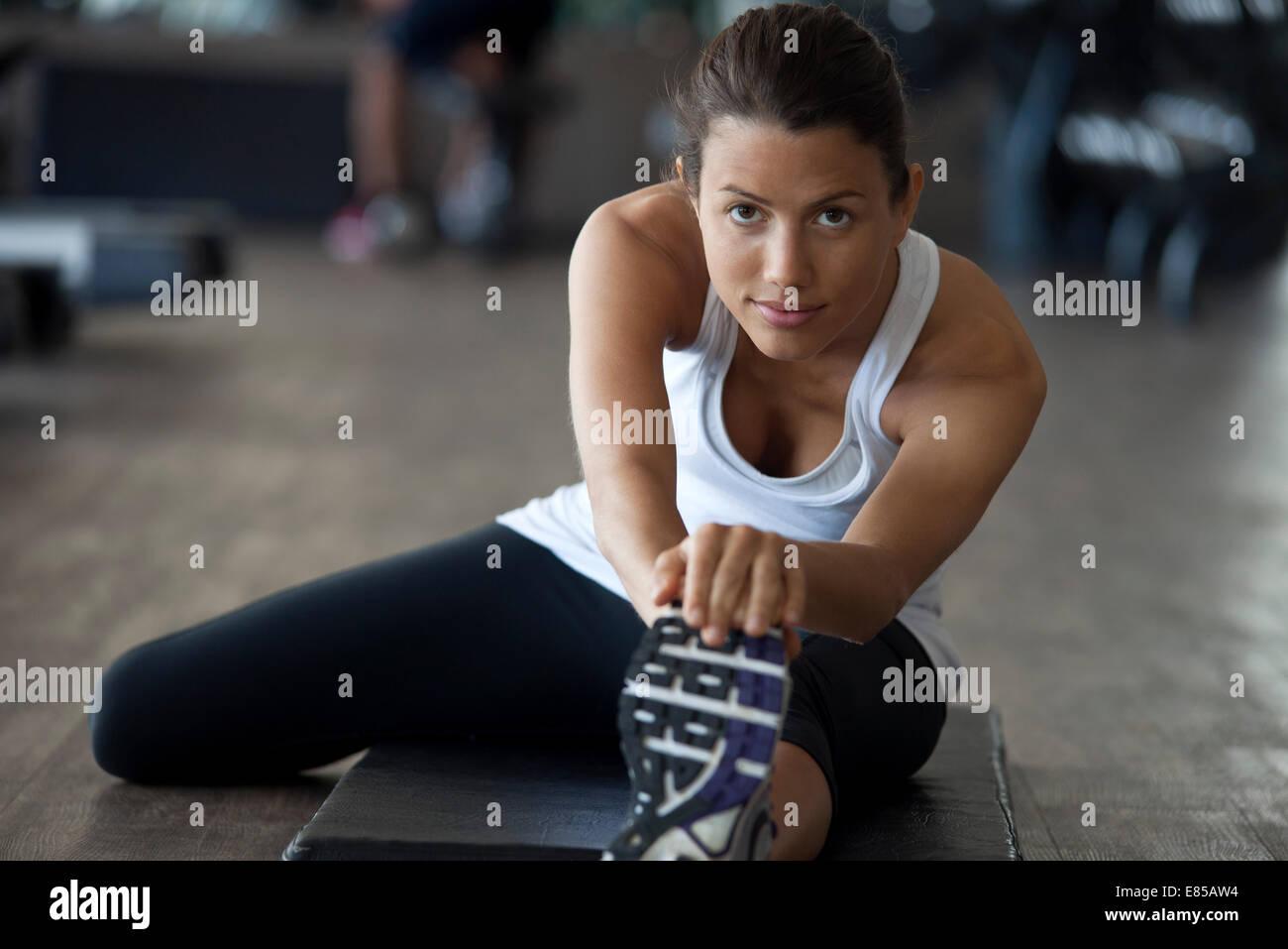Frau in Turnhalle Aufwärmen mit Bein Strecken Stockbild