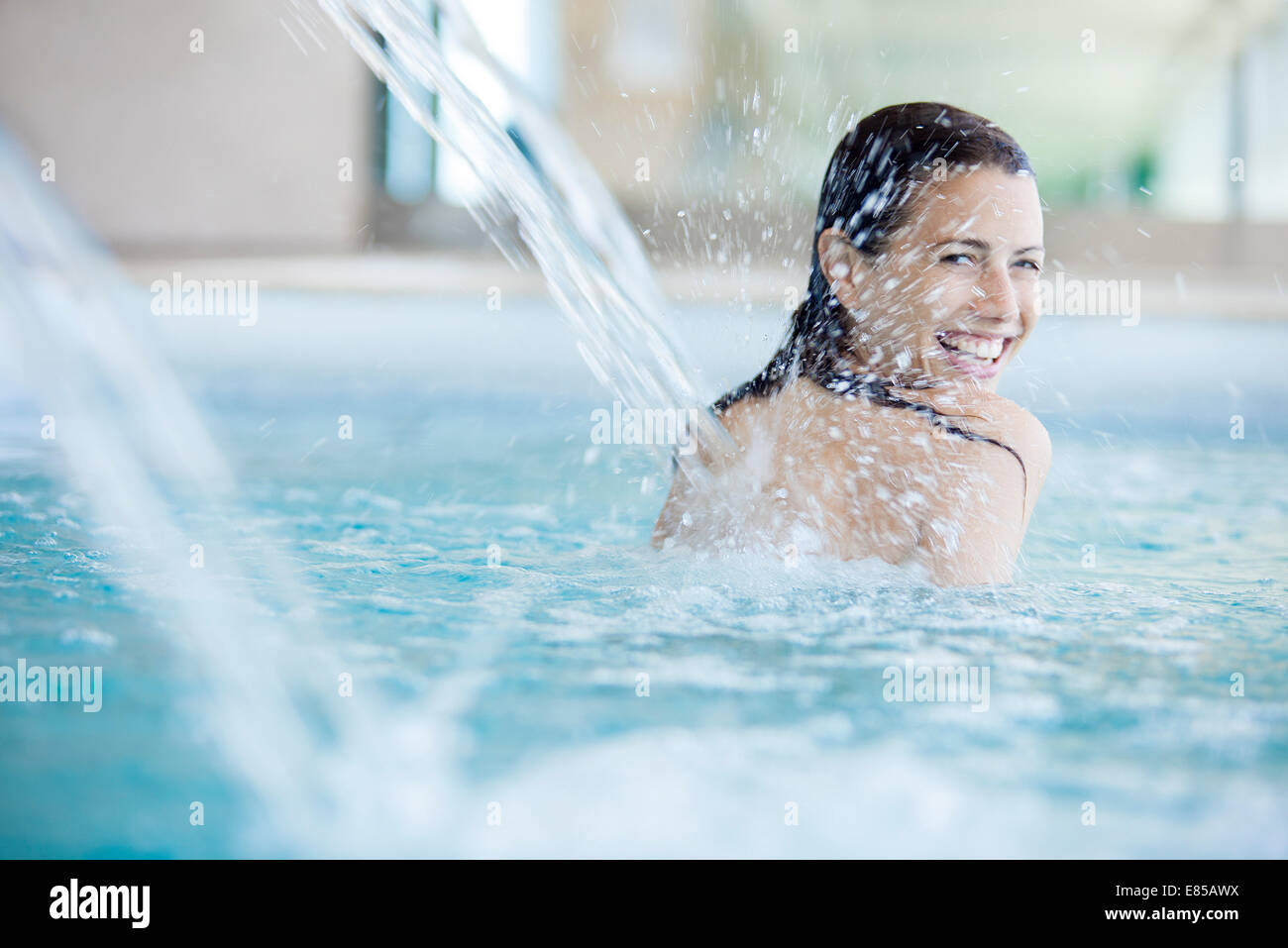 Frau unter Brunnen im Schwimmbad Stockbild