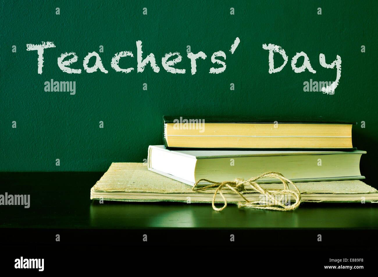 der Text Teachers Day mit Kreide auf einer grünen Tafel und einige Bücher auf dem Schreibtisch geschrieben Stockbild