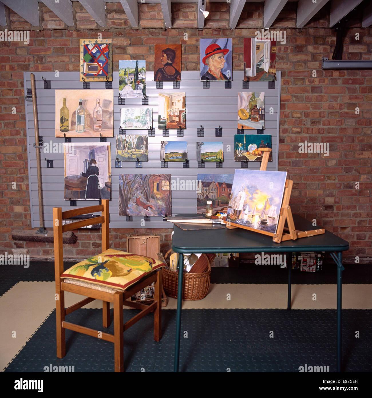 Stuhl Und Tisch Mit Gemälden An Wand In Garage In Künstleratelier  Konvertiert Stockbild