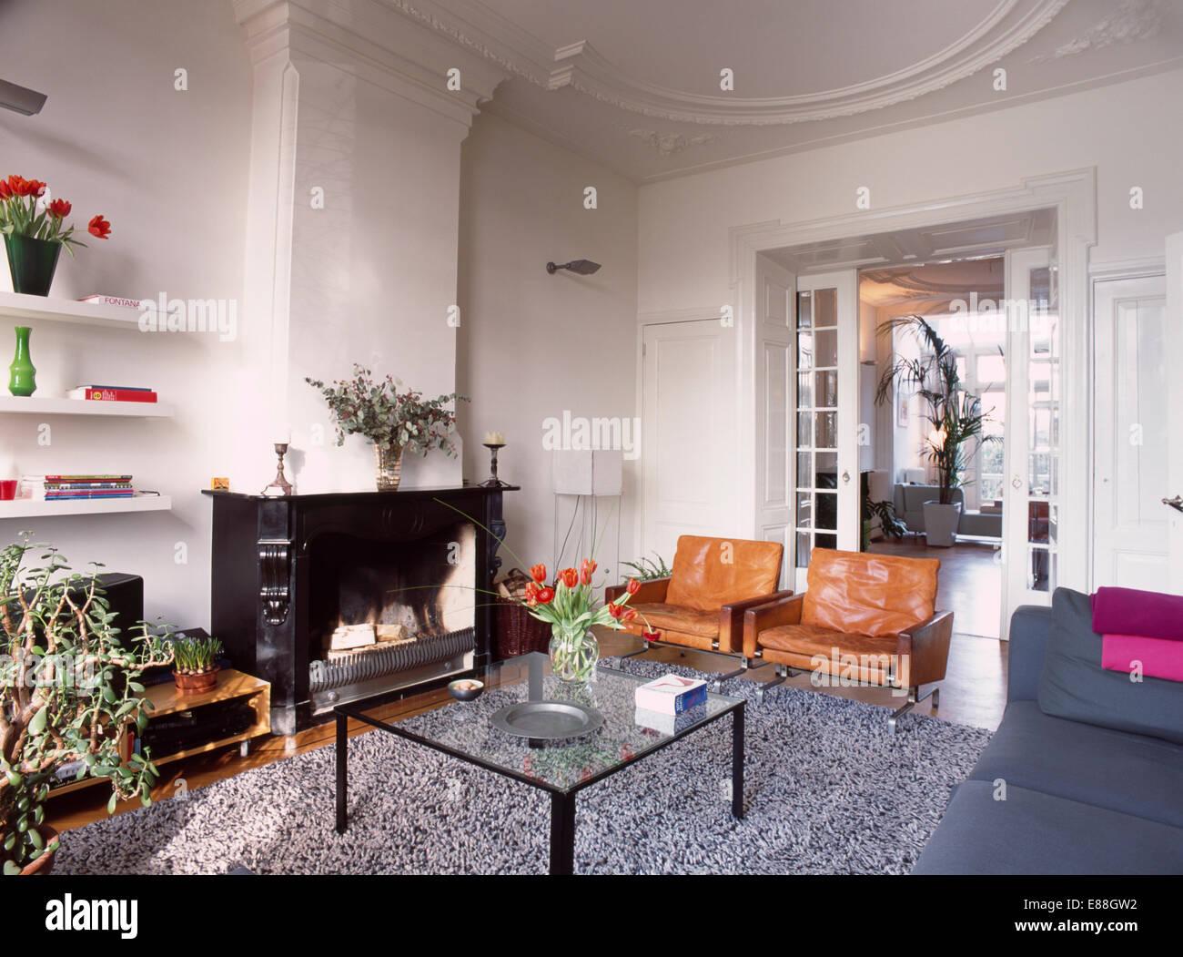 Fantastisch Texturierte Graue Wolldecke Und Modernes Glas Tisch Und Leder Stühle Im  Traditionellen Wohnzimmer Mit Schwarzen Kamin Und Glastüren