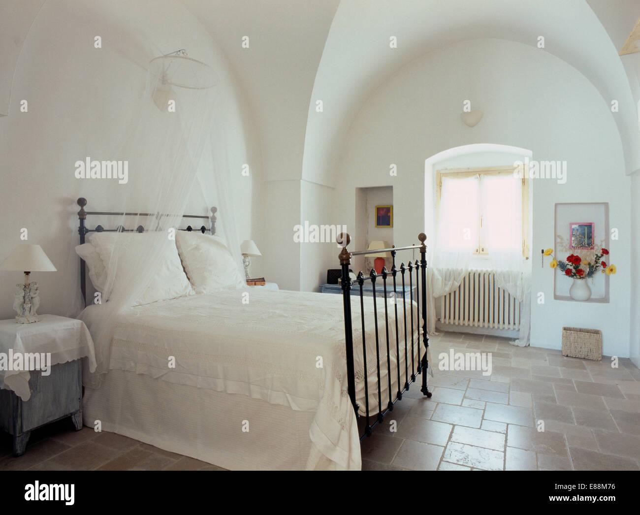 Weiße Bettwäsche und Moskitonetz auf Schmiedeeisen Bett in ...