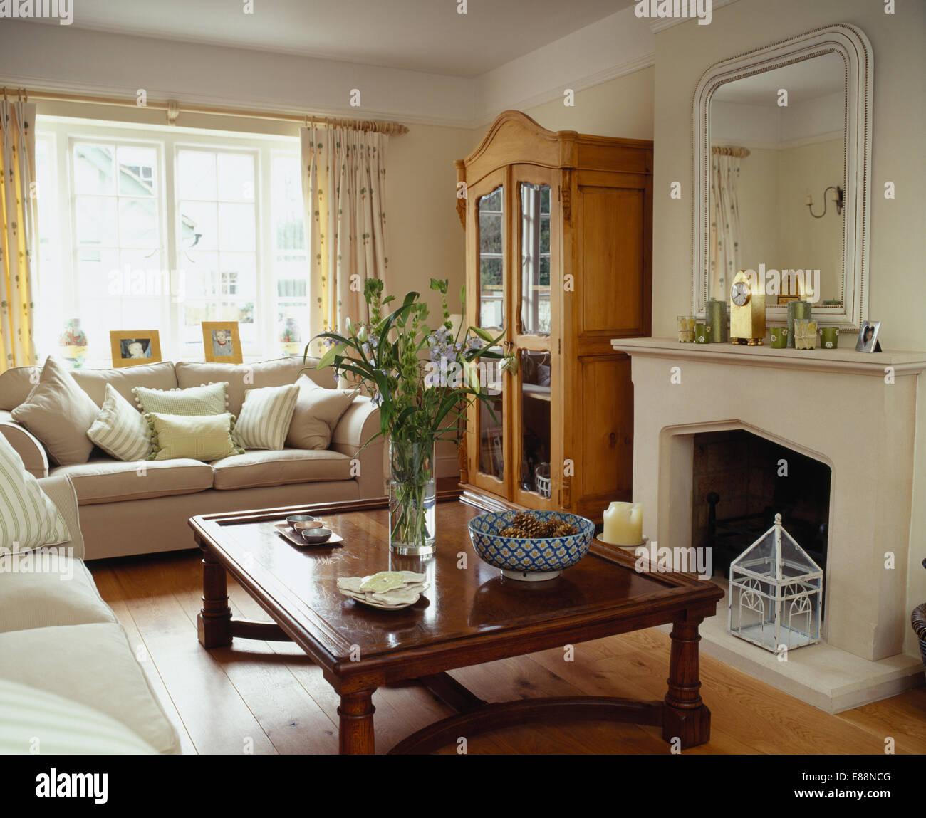 Indonesische Holz Couchtisch Kamin Im Wohnzimmer Mit Cremefarbenen Sofas Und Glasfront Kiefer Schrank