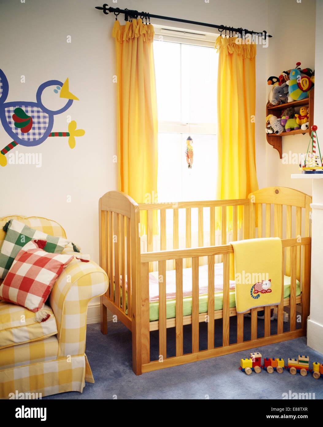 Kinderbett aus Holz vor Fenster mit gelben Gardinen im ...