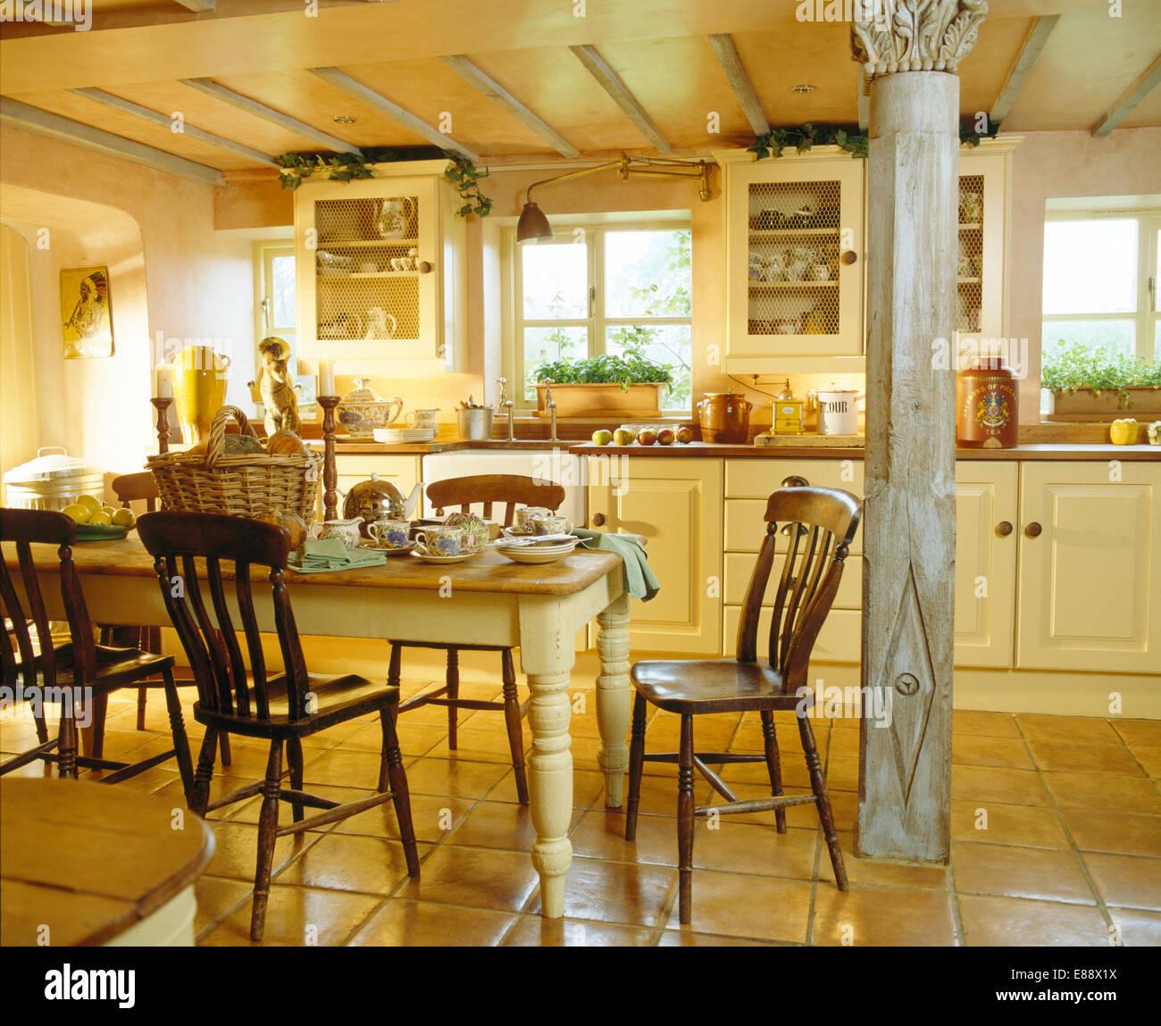 Alte hölzerne Stühle an gemalten Tisch im Cottage-Küche mit ...
