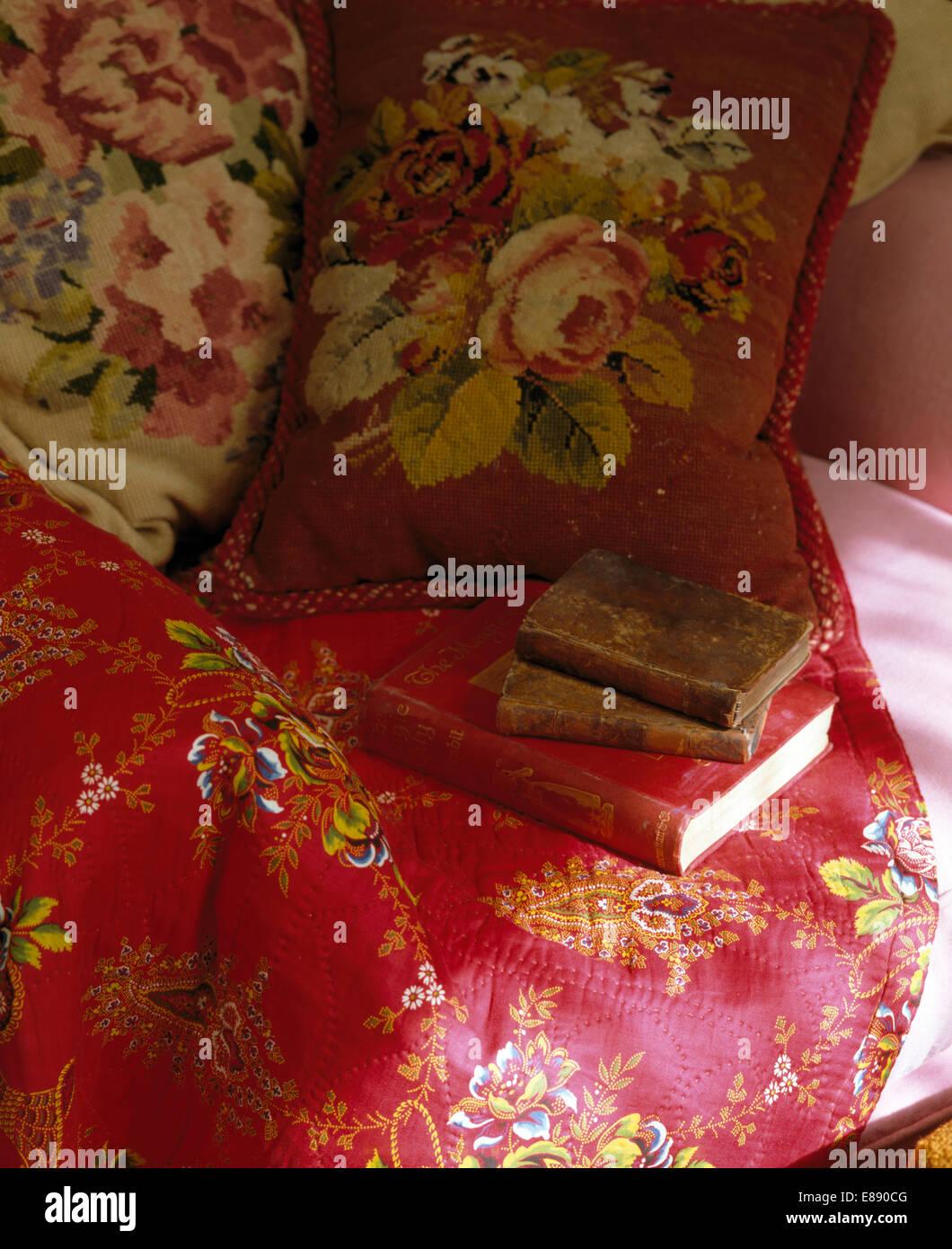 048f4865bb Nahaufnahme von Gobelin Kissen und alte Bücher auf Stuhl mit roter Seide  werfen Stockbild