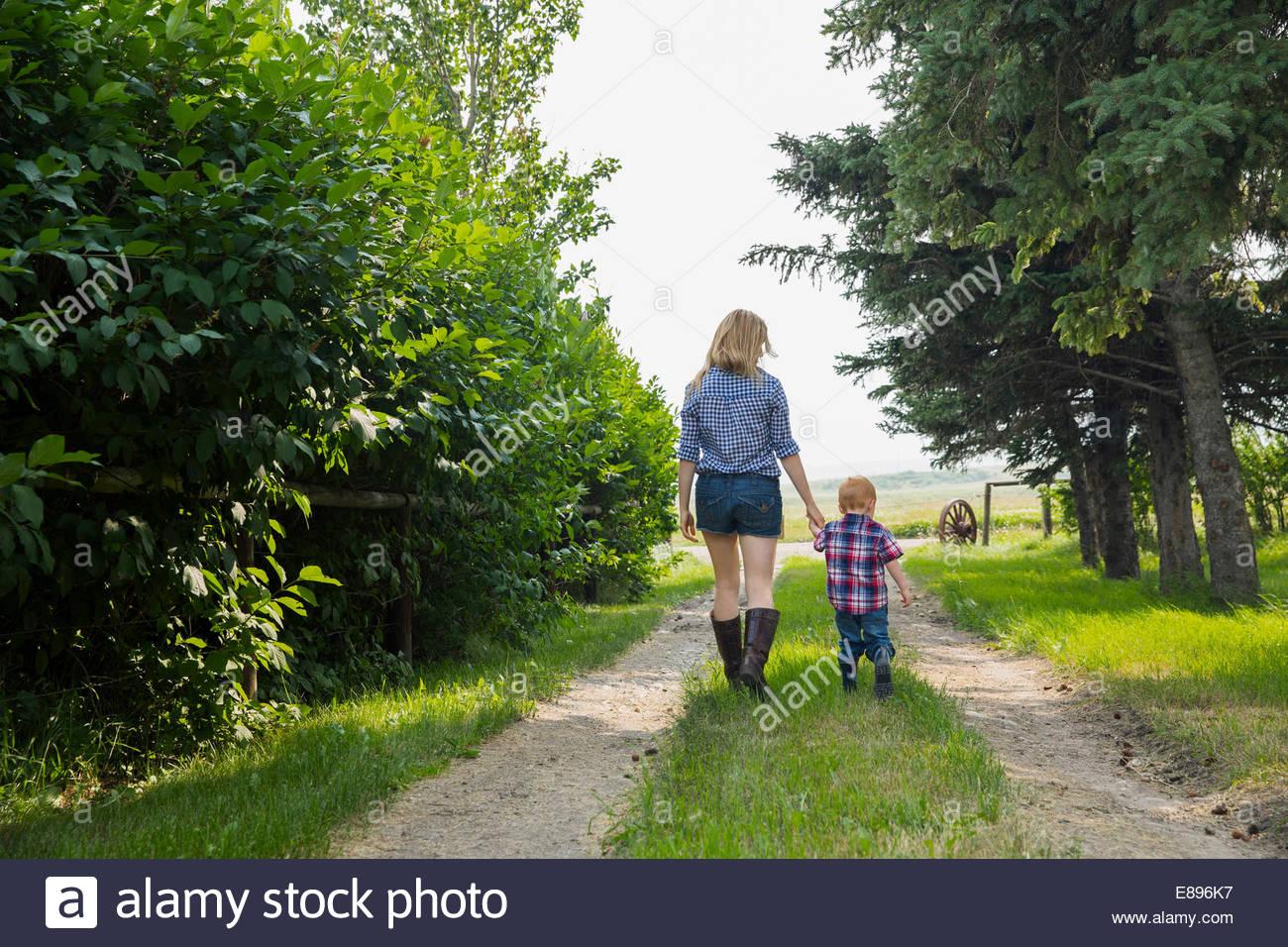 Mutter und Sohn gehen auf Landstraße Stockbild
