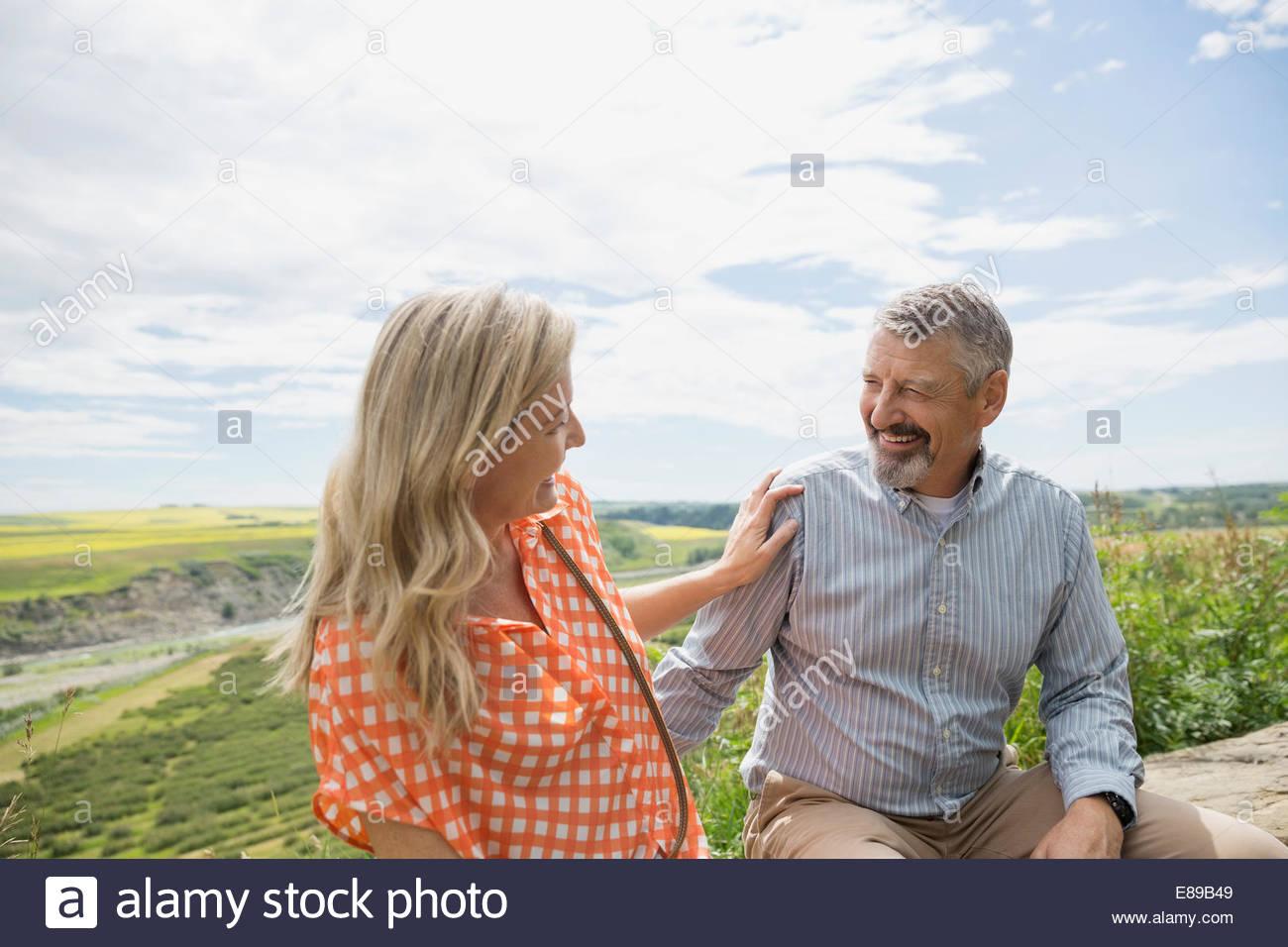 Paar im Freien mit Landschaft im Hintergrund lachen Stockbild