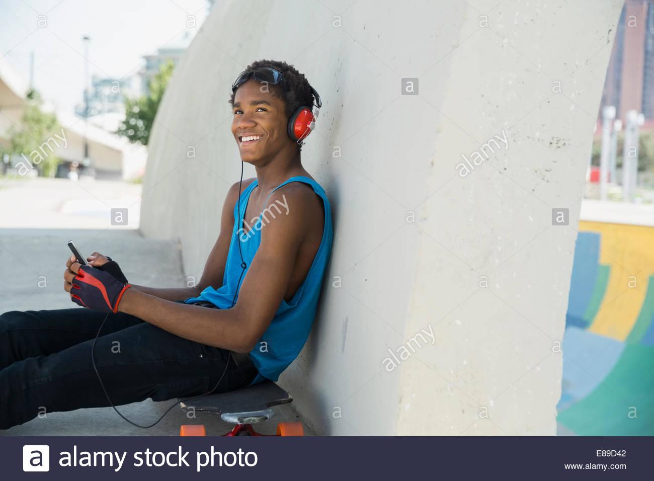 Teenager mit Handy und Kopfhörer auf skateboard Stockbild