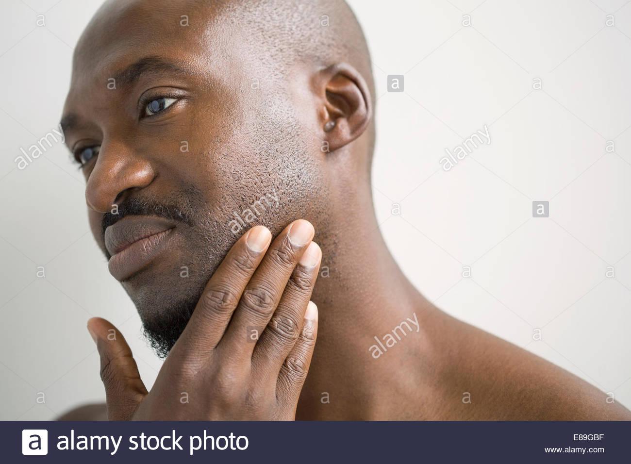 Nahaufnahme des Mannes reiben Stoppeln auf Gesicht Stockbild