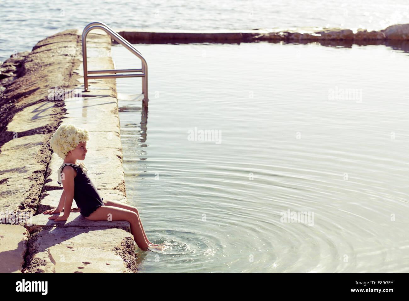 Mädchen in der Blüte Kappe sitzen am pool Stockbild